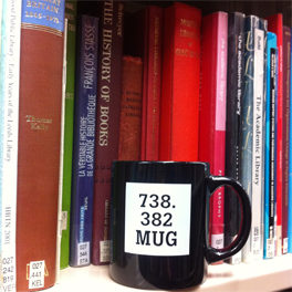 Dewey Decimal themed mug on a library bookshelf